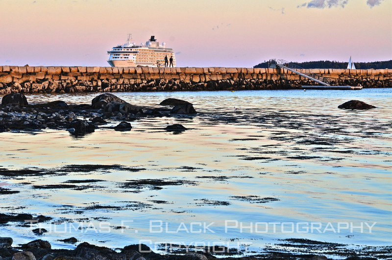 Same cruise ship, now basking in purplish twilight. Look closely and you will see couple walking past it on breakwater. Sailboat is in distant background, to right. [UFP101312]