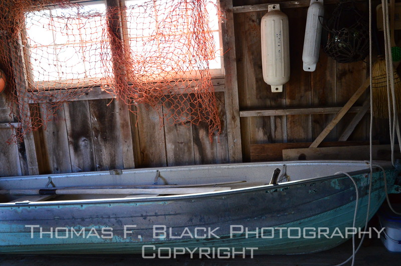 "Lobsterperson's dinghy languishing in shed at New Harbor. What caught my eye were the contrasting colors and especially the makeshift orange-colored window ""treatment."" [UFP101112]"