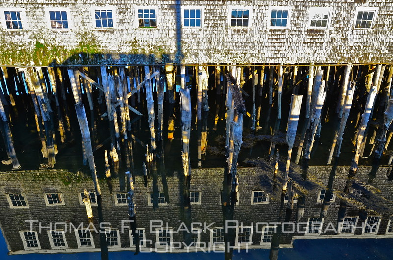 What the heck is this?! Granted, it may cause visual confusion, at least initially. The bottom half is a water-reflected mirror image of a shingle-sided boat house in New Harbor. Photo was taken from the edge of a parallel pier. [UFP101112]