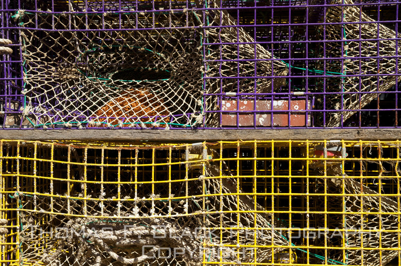 Clutch of traps in repose on dock in Owl's Head, deposited there after day's catch was delivered to waiting wholesale vendors. Bricks, visible in top two, are employed to prevent traps from bobbing to the surface, an occurrence not good for business.  [UFP092012]