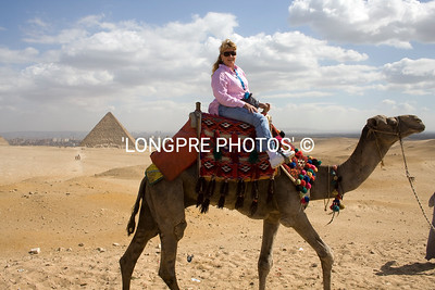 Photographer riding camel around Pyramids.