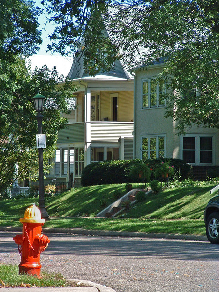 """We lived on the ground floor of the duplex on the left. This lot was flat, but the yards adjoining were terraced. Sign on lamppost: """"Lexington-Hamilton Neighborhood""""."""