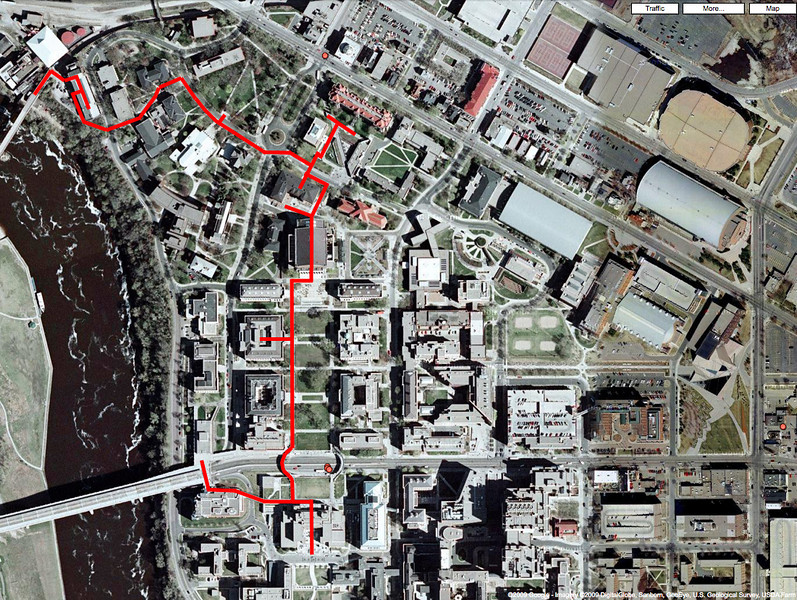 Satellite photo of the Twin Cities Campus (East Bank) showing (in red) the route taken from Coffman Student Union (at bottom, south of Washington Avenue), northward up the Mall to Northrop Auditorium and to Folwell Hall (which fronts on University Avenue), then westward through the historic Knoll, where the U's oldest buildings are located. Washington Avenue bridge spans the Mississippi River at lower left.