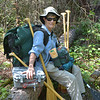Beth takes a break during the 1 mile long portage of gear toward Crab Lake.