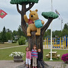 """Some grandchildren pose at the """"Winnie the Pooh Tree"""" and park in White River, Ontario.<br /> Here in 1914, an orphaned female black bear cub was purchased from a trapper by Lt. Harry Colebourn, a Canadian Army Veterinarian on his way overseas.  Named after his hometown, Winnipeg, Manitoba, she became the regiment mascot but was left for safekeeping at the London Zoo where she became a favorite of Christopher Robin and his father, A.A. Milne."""