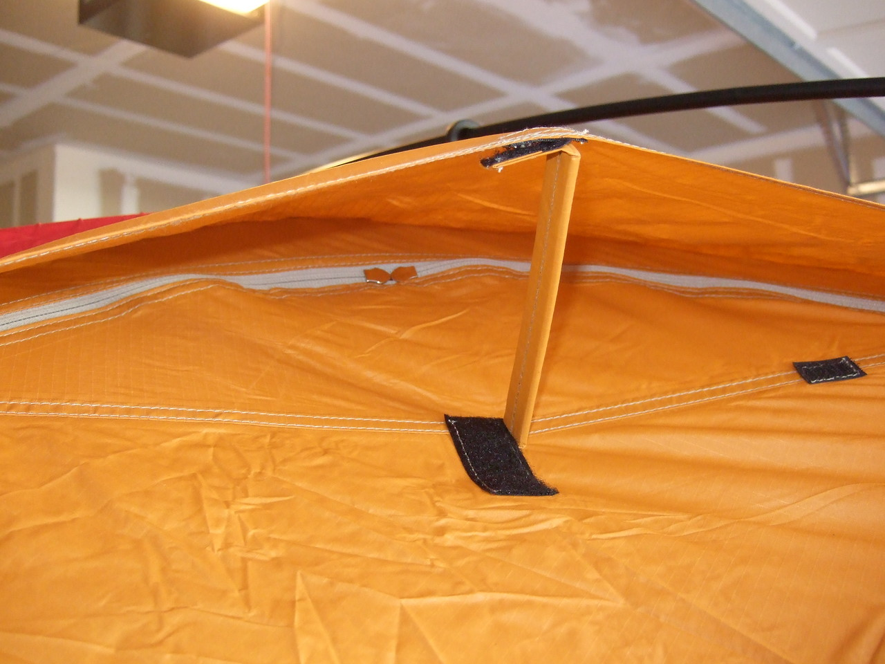 Underneath the flap is a small stiff piece that you raise and stick to the velcro as shown. Under that flap is another zippered flap which is closed in this photo, sealing the fly against dust.