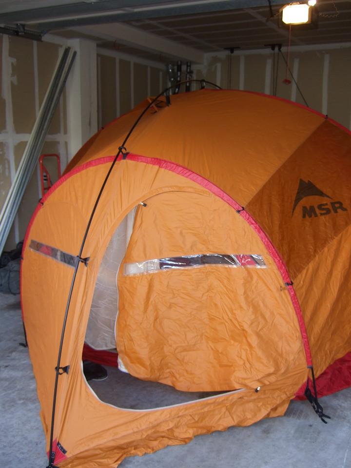 This is an overview of the tent from the open garage door, with the fly door unzipped. It is a large tent, taking up as much room as a car. Three poles run through the red tunnels; you can see one end tunnel over the fly door, and another tunnel is at the peak of the tent. The fourth pole clips the length of the fly on caribiners and holds the vestibules out.