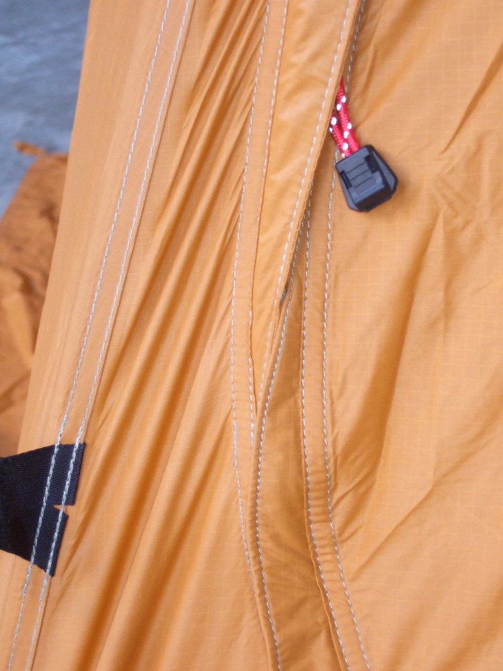 The zipper pull is here to call attention to that nice detail. The zipper has a flap over it that is on the outside of the door to shed water until the zipper makes a turn near the bottom of the tent. Then that little flap is on the door itself so tht water runs over the zipper instead of down into it. Nice touch.