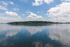 Clouds above island in the Saint Lawrence reflected in the water.