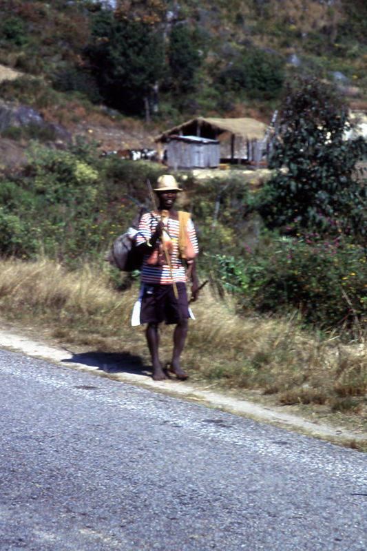 Man walking along road with lunch and machete, Madagascar.