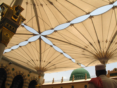 The green dome is part of the original Prophet's Mosque built by the  Ottomans.  The umbrella structures and arcades in the foreground are part of a large extension completed in the 90s.  The umbrella structure is unique; opening at a press of a button to provide much needed shade from the Saudi heat for worshippers within the Mosque's main courtyards.