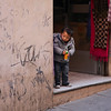 Lot's of chinese in Madrid, running grocery- and clothes shops. <br /> This boy was just standing in the door of his parents' shop, checking out his street, while enjoying his refreshment...