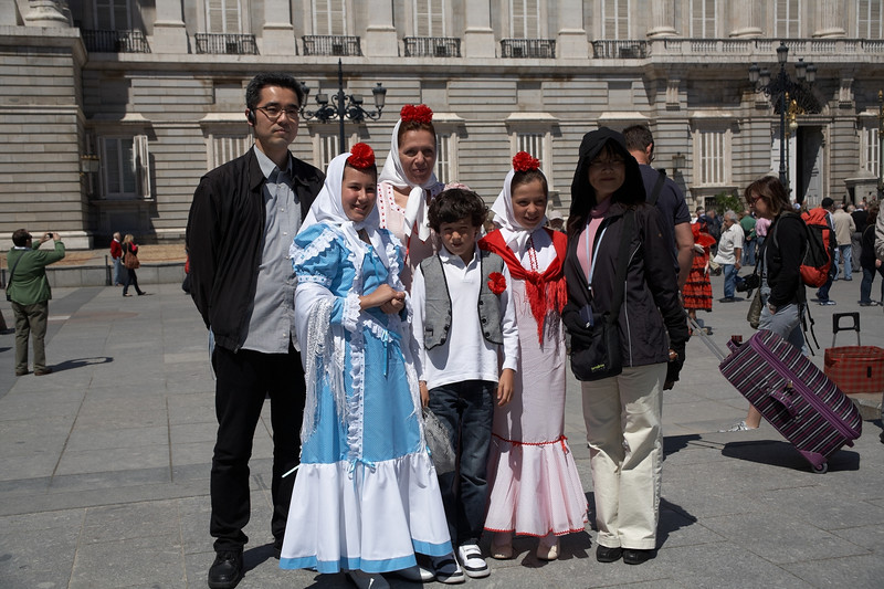 Two Asian tourists get a snapshot with some Spaniards in traditional dress.