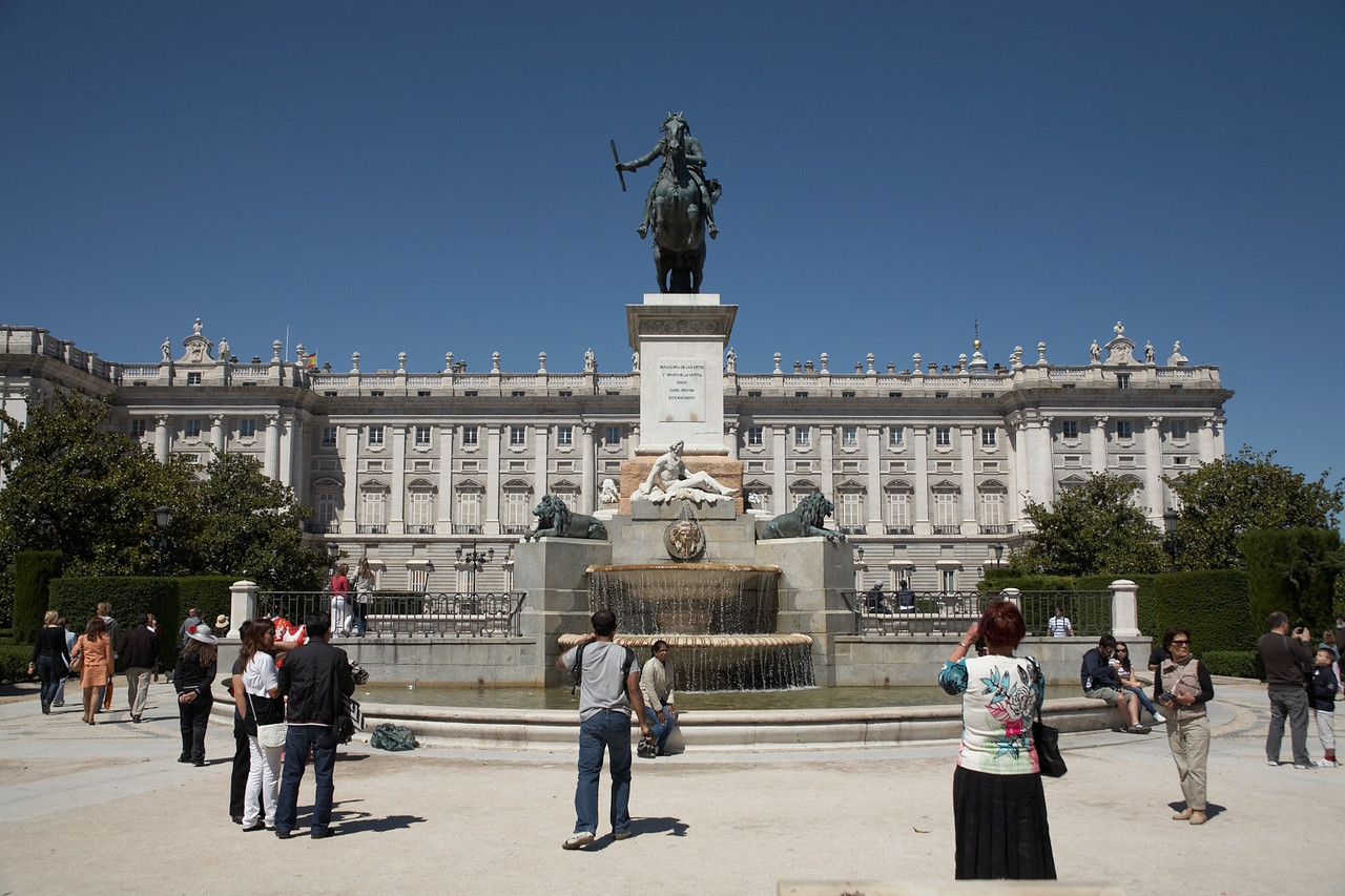 This is a wider view of the Plaza de Oriente with the statue of Felipe IV. The Palacio Real is in the background. There are several more statues to the left and right.