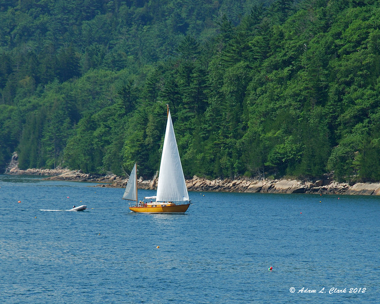 A sail boat coming in pulling a smaller boat