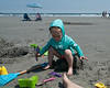 Sitting on Daddy's sand castle... and making it collapse