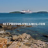 A view from the rocky shore towards a cruise ship in Frenchman Bay, Bar Harbor, Maine.
