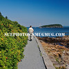 A man looks towards the ocean while walking on Bar Harbor's Shore Path, Maine