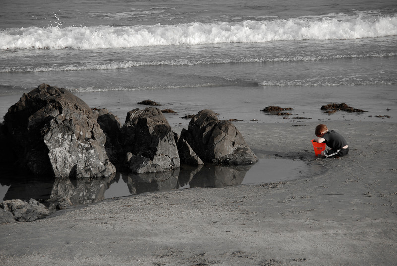 Red Bucket<br /> A kid playing in some tide pools, shortly before the tide came in.
