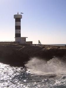 Wild sea as cyclist heads for the lighthouse