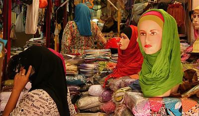 Let op detail: de mobiele telefoon laat zich ook tussen de hoofddoekjes zien. Little India, Kuala Lumpur, Maleisië.