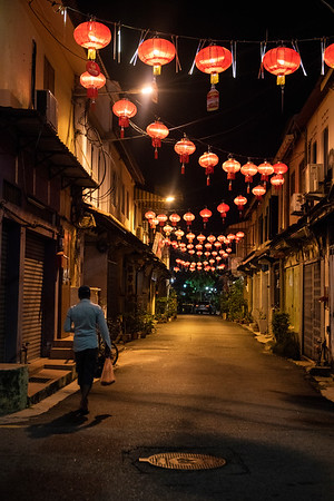 A man walks home along a quiet street dotted with red lanterns left over from Chinese New Year in Malacca, Malaysia.