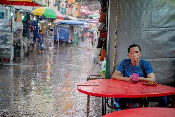 A man eats dinner while waiting out a monsoon storm in Kuala Lumpur's Chinatown.