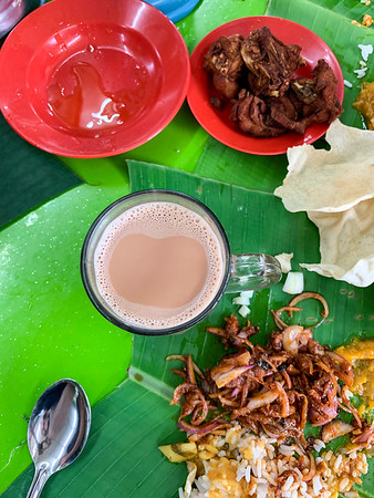 A typical banana leaf rice lunch on the outskirts of Kuala Lumpur, Malaysia. No plates are served here, but instead diners are presented with large banana leafs to pile their rice, curry, sambal anchovies, and fried chicken on. Teh tarik, a combination of condensed milk and tea and Malaysia's national drink, is a common accomplice in this feast.