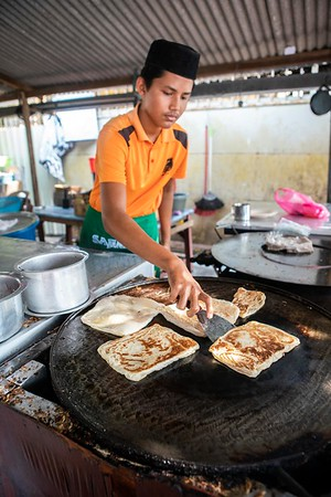A young boy flips fresh roti at a traditional restaurant in Malacca, Malaysia. Roti and teh tarik are traditionally served together at these roadside stops.