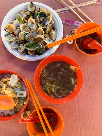 A Peranakan meal  of laksa (noodle soup) and ginger clams at a night market in UNESCO World Heritage City of Malacca, Malaysia.
