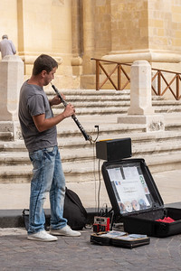 Street musician. One does not often see an oboist on the street.