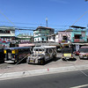 Jeepneys and transport vehicles along the street and stores in Manila, Philippines.