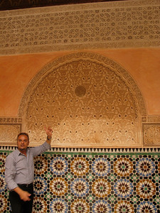Idriss, our guide, explaining the three elements of the building: tile, carved stucco, and carved cedar.