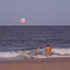 Boy watching the moonrise over the ocean surf at Ocean City Md