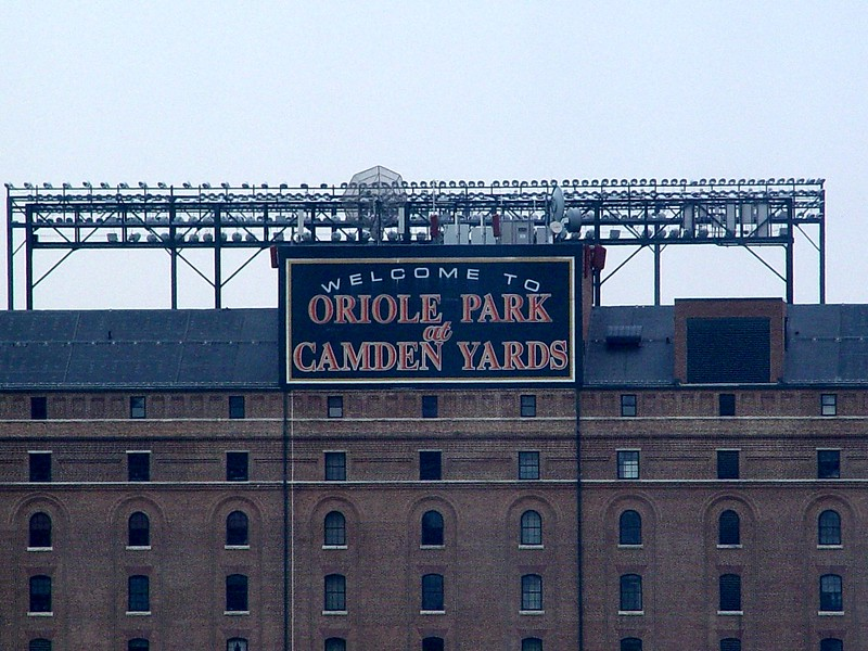 """<b>Oriole Park at Camden Yards</b>, the beautiful baseball-only facility in downtown Baltimore, became the official home of the Baltimore Orioles on April 6, 1992. The construction of the park was completed in essentially 33 months from the time they began razing the previous structures on the 85-acre parcel, which began June 28, 1989, in the area known as Camden Yards, the one-time railroad center.    It is only two blocks from the birthplace of baseball's most legendary hero, George Herman """"Babe"""" Ruth. Ruth's father operated Ruth's Cafe on the ground floor of the family residence located at Conway Street and Little Paca, now center field at Oriole Park at Camden Yards.   The ballpark seats 48,876 (including standing room) and the project cost was approximately $110 million.  (This photo was taken from my hotel room.)  (July 31, 2006)"""