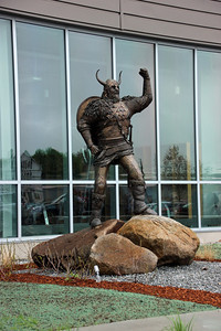 """The Viking is the school's mascot. Chris Williams, a metal sculptor from Essex, sculpted this eight-foot tall bronze statue of the school's mascot, which stands at the main entrance of the Harold E. and Marilyn J. Gassett Fitness and Recreation Center. Made entirely of bronze and weighing nearly 1,000 pounds, the sculpture is a product of seven months of labor by Williams, who noted that it was a process involving not only the sculpting itself, but also the opportunity to hone its focus. """"We really wanted to capture the spirit of the school,"""" Williams commented. """"After going back and forth, and putting everything in place, I think the statue really does that by being strong."""""""