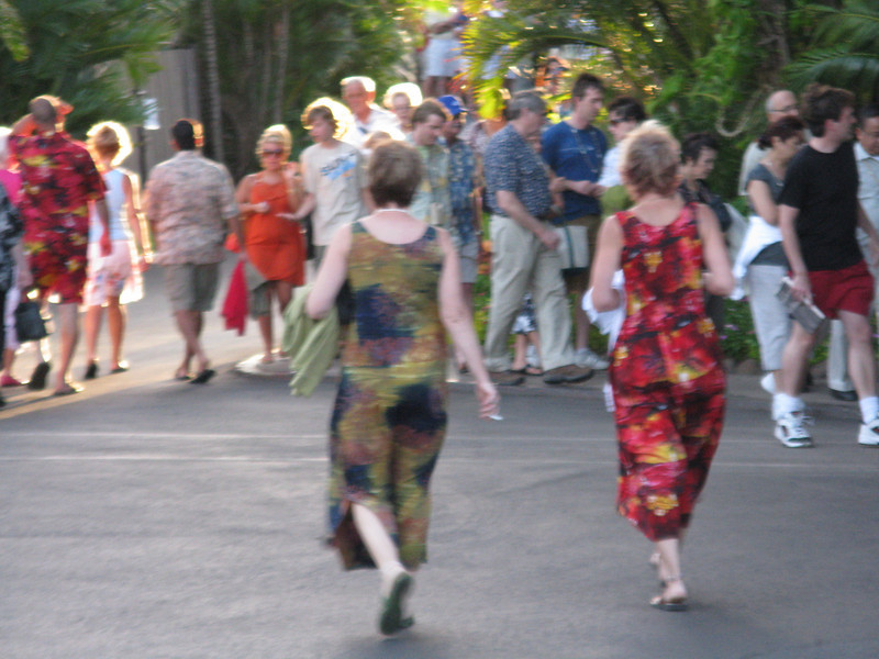 Man on left and woman walking on right with matching outfits as we enter the Luau.