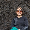 Mary leaning against a lava wall, watching the surf roll into the black sand beach.