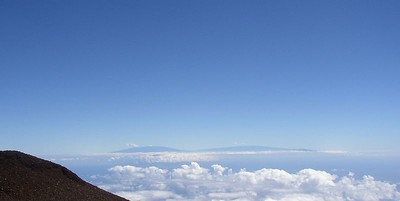 Hawaii peeking above the clouds in the distance.