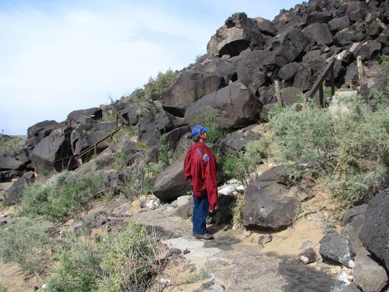 Rain clouds findly drifted awayed letting the air warm up a bit. Dave taking in more petroglyphs along Cliff Base Trail.