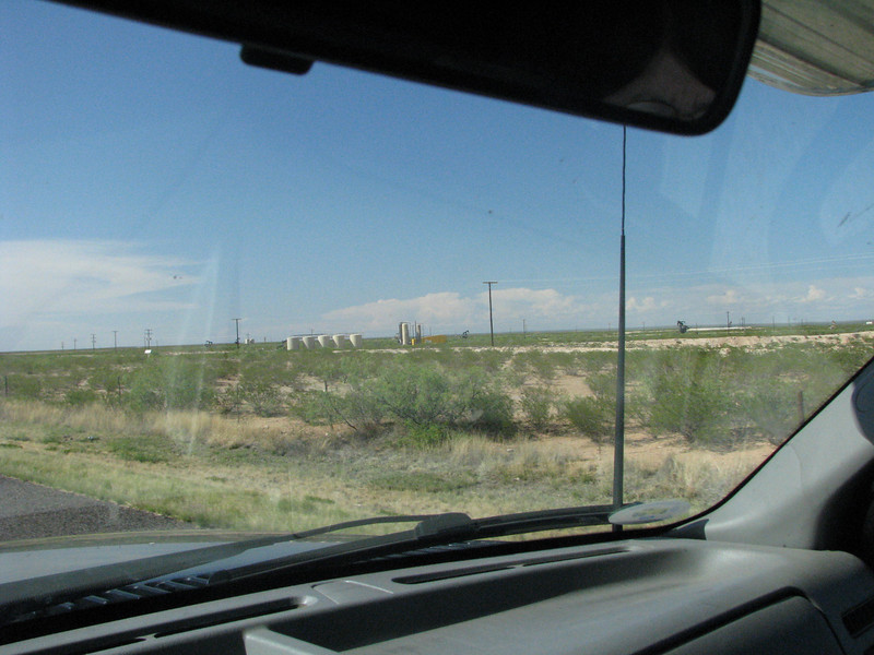 A few storage tanks and oil pumpers seen in the near distance.