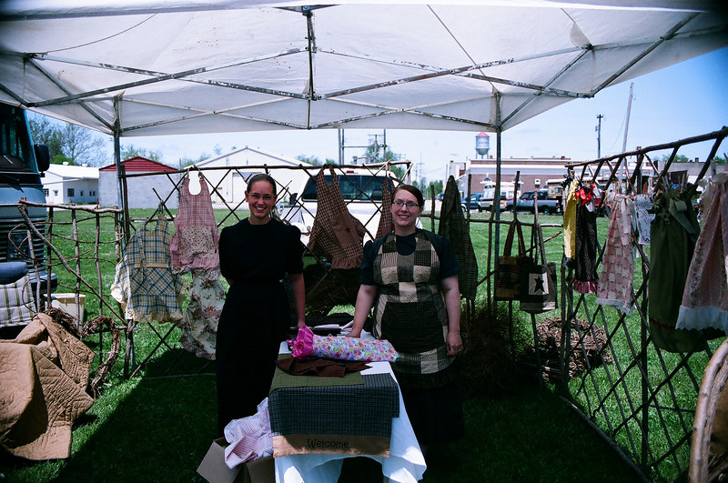Two young ladies of the Mennonite faith selling their hand crafted goods.