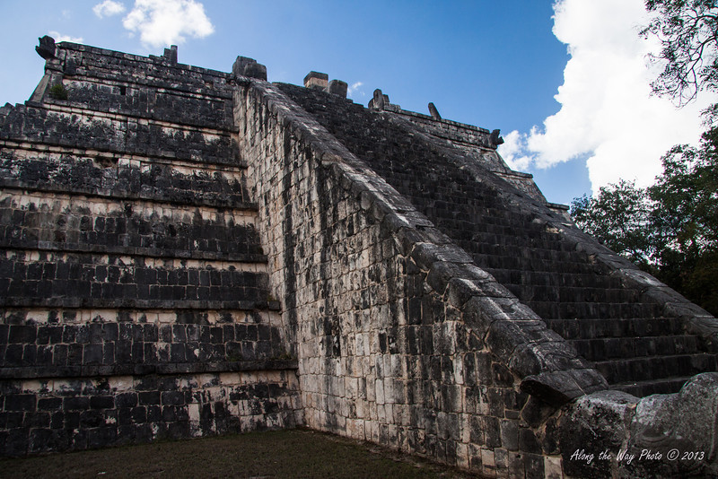 Yucatan-9592<br /> The Tomb of the Great Priest, at Chichen Itza, has a communal grave yard under its foundation. This structure has three platforms. The platform of the tombs has six columns, houses two tombs and has a frieze showing serpents.