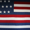 """US flag, Naval Academy<br /> <br /> Based on eyewitness account, this flag was flown by Captain John Paul Jones aboard the frigate RANGER in 1778, when he sailed into quiberon Bay. The French fleet fired a nine gun salute to become the first time a foreign gevernment recognized the """"Stars and Stripes."""""""