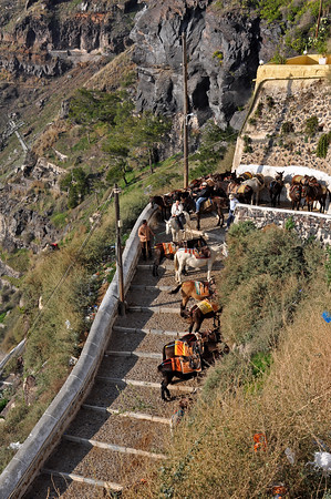 Not far from the top, mule handlers wait for fares who start out walking, then realize they have a very long way to go. Two tourists (mounted) decide a ride might be easier than the walk. Santorini, Greece