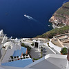 Looking straight down to the harbor at a tender boat going back to the cruise ship. Rooftops made into terraces. Santorini, Greece