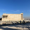"The design is not that of a ""typical"" Greek temple.  It is not flat, but is built on two levels, due to its position on the side of a hill.  If you stand beside the north wall of the Parthenon this is the view of the Erechtheion you would see.  The temple housed the cults of two gods:  Athena and Poseidon, plus it was believed to contain the graves of two mythical kings, Erechtehos and Kekrops.  This was also considered by Athenians to be the spot where Athena and Poseidon had a fight over who was going to be the patron of Athens.  Each offered the Athenians a gift.  Athena offered the olive tree, representative of the area's agricultural wealth, and Poseidon offered the sea, with its strategic position along the Aegean trade routes.  The Athenians, obviously, picked Athena and so the contest was decided."