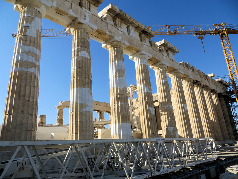 "The light portions of the columns are new pieces of marble.  Over time they will weather to match the older pieces.  The new stones must be cut to fit exactly as no two columns are alike.  If you look closely you can see that the columns are built of ""drums"" of marble.  Each drum has a square hole in the center, through which is inserted a metal rod to hold them together.  The original builders enclosed the rods in lead.  Restorers in the early 20th century used iron rods to replace them; the iron rusted and cracked the marble, leading to extensive damage.  New rods are titanium."