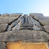 """It is estimated that the lintel stone weighs 18 tons.  The construction over the door lintel is characteristic of Mycenean architecture.  The blocks of the wall are so placed  that each projects a little farther out than the one below it, thus creating an empty triangular space over the lintel.  This is known as the """"relieving triangle.""""  This relieves the lintel from the weight of the heavy wall above it.  The relieving triangle of this gate, of course, is filled by the lion sculpture."""