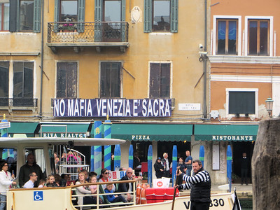 "While standing on the Rialto Bridge, I saw this intriguing sign.  My Italian is rudimentary but I think it says ""No mafia, Venice is sacred.""  Curious about it, I Googled it when I got home.  It seems to date from several years ago when  there was a huge corruption scandal and the mayor was arrested.  Earlier photographs of the sign show it reading ""Stop Mafia, Venice is sacred.""  For that matter, there used to be an exclamation point after Mafia! which has mysteriously disappeared.  I also learned that this sign is so much of a ""thing"" that you can buy coffee mugs and T shirts with this on it."